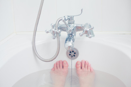 Closeup on the feet of a young woman in a bathtub photo