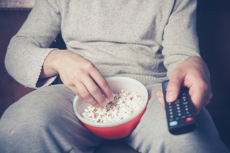 Young man is sitting on a sofa and eating popcorn while watching television Stock Photo
