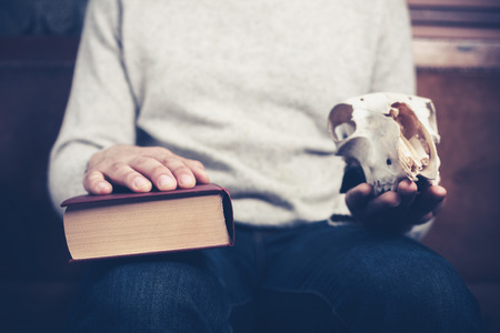 existentialism: Young man is sitting on a sofa with a book and an animal skull