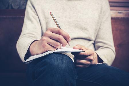 Um homem está sentado em um sofá e escrever notas em um caderno Imagens