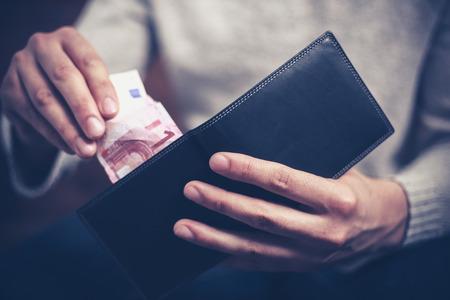 Close-up op een man krijgt geld uit zijn portemonnee Stockfoto