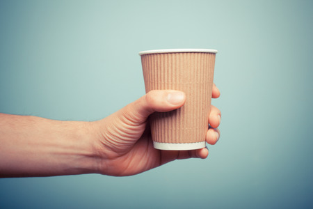 A man is holding a brown paper cup Stock Photo