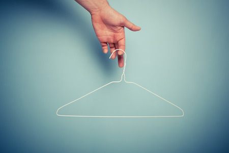 laundry hanger: A Hand is holding a wire hanger