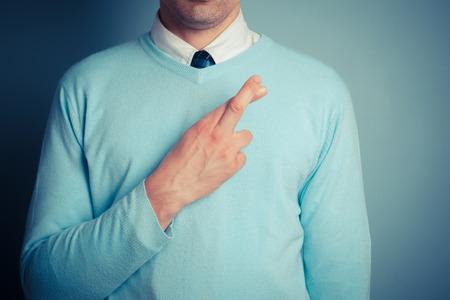 honestidad: Hombre joven con los dedos cruzados sobre su coraz�n