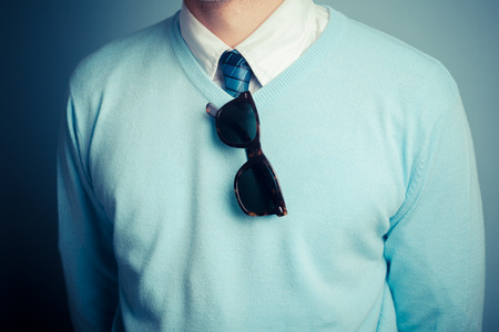 preppy: A smartly dressed young man with a pair of sunglasses