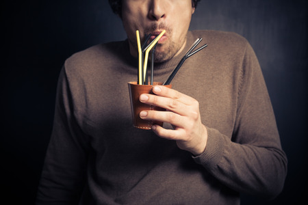 A silly young man is drinking from a leather cup with a bunch of colorful straws photo