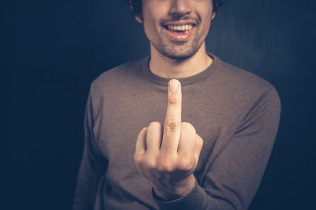 obscene: Young man is displaying an obscene gesture