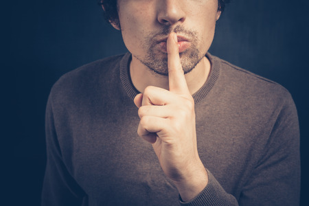 signalling: Young man is signalling hush with his finger on his lips Stock Photo