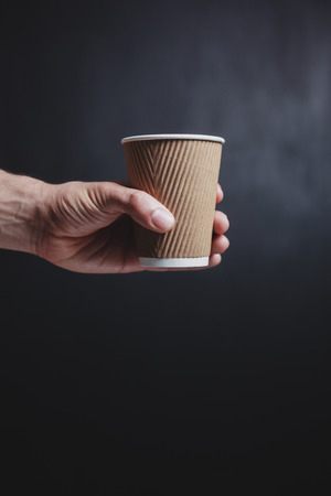 Close up on a young man s hand holding a paper cup photo
