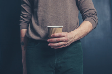 Young man is  holding a brown paper cup photo