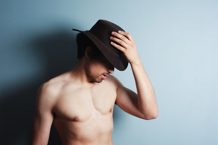 A sexy shirtless young man is wearing a cowboy hat photo