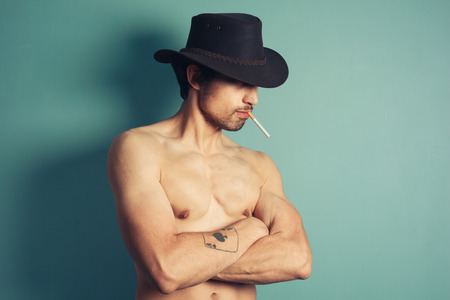 A sexy shirtless young cowboy is smoking a cigarette photo
