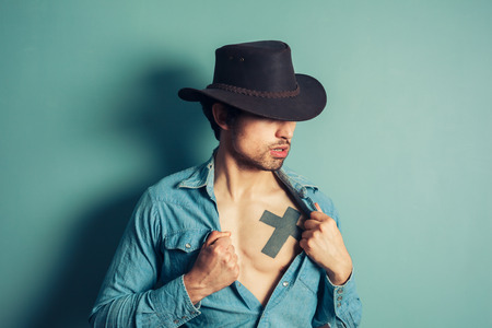 Young cowboy is unbuttoning his shirt to reveal a tattoo on his chest photo