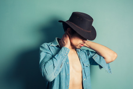 A sexy young cowboy is standing by a blue wall with his shirt unbuttoned