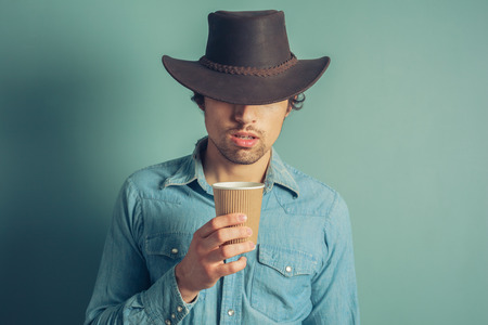 Young cowboy is drinking coffee from a paper cup photo