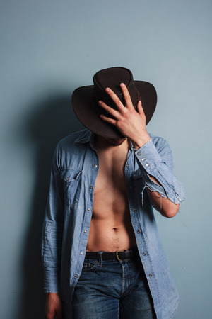 Sexy young cowboy by a blue wall is standing with his shirt open Reklamní fotografie