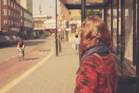 bus stop: A young woman is waiting at the bus stop on a sunny day