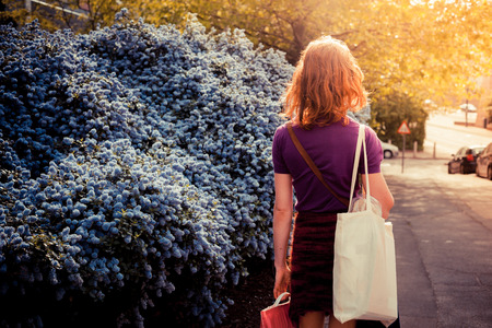 Young woman with shopping bags is walking in the street on a sunny day photo
