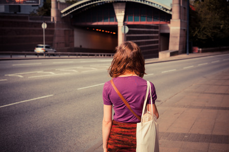 A young woman is walking by the side of a busy road on a sunny afternoon photo