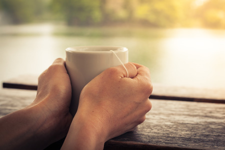Closeup on a womans hands holding a cup of tea by a lake in the afternoon Standard-Bild