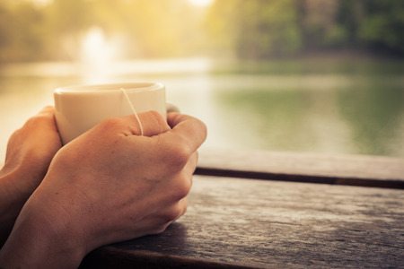 morning tea: Closeup on a womans hands holding a cup of tea by a lake in the afternoon Stock Photo