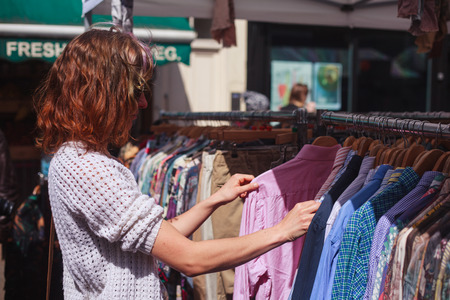street market: A young woman is browsing a rail of clothes at a street market
