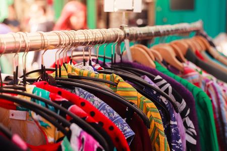 tienda de ropa: Clotes colgando de un ferrocarril en un mercado callejero al aire libre