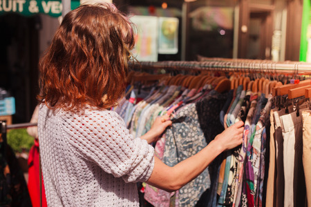 젊은 여자가 거리 시장에서 옷 레일을 검색한다