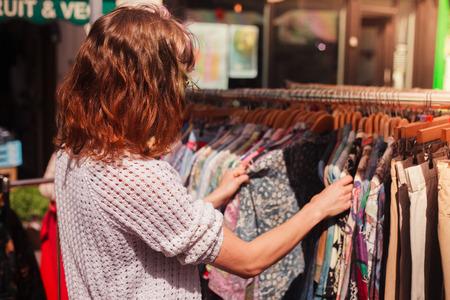 tienda de ropa: Una mujer joven está mirando un carril de la ropa en un mercado callejero