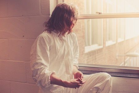 boiler suit: A young woman in a white boiler suit is sitting by a window
