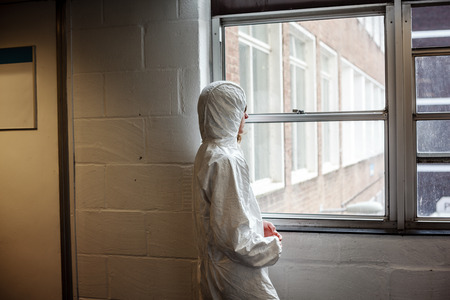 boiler suit: A scientist wearing a boiler suit is standing by  a window