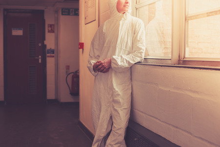 A scientist wearing a boiler suit is standing by  a window photo
