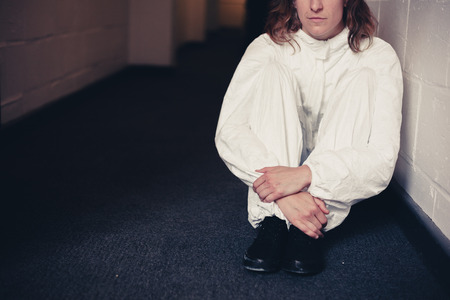 boiler suit: A woman wearing a boiler suit is sitting in a corridor Stock Photo