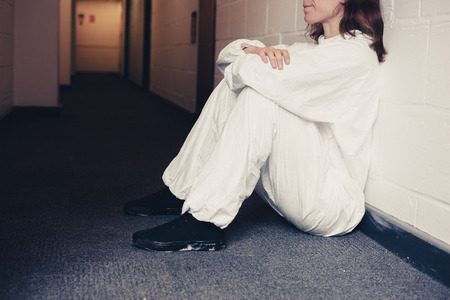boiler suit: Young woman wearing a boiler suit is upset and is sitting in a corridor