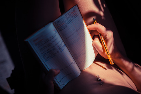 Young naked woman is writing in a notebook photo