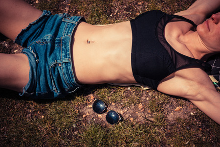 A young woman is lying in the grass on the ground and relaxing photo