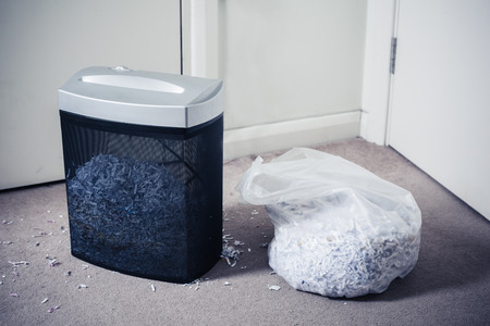 A paper shredder and a bag of shredded documents by the door photo