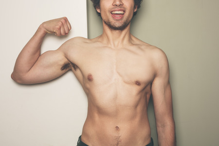 dual: A young athletic man is flexing his muscles against a dual colored  Stock Photo