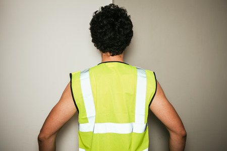 Rear view of a builder in a high visibility vest against a green and white