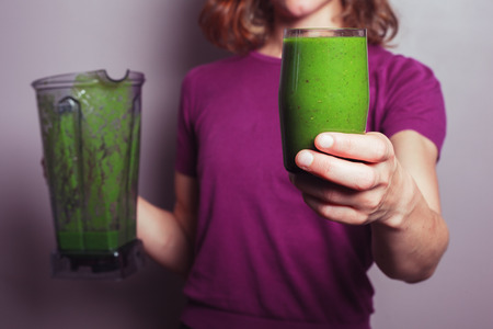 A young woman in a purple top is holding a blender and a glass with green fruit smoothie photo