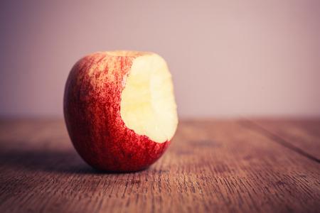 apple bite: A half eaten apple on a wooden table