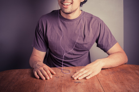 A young man is sitting at a table with earphones in his ears and is listening to music photo