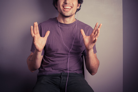 A happy young man is listening to music through his earphones photo