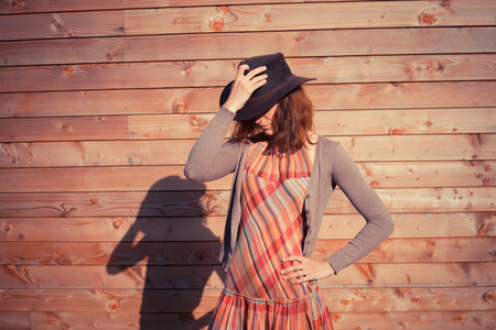A young woman wearing a cowboy hat is standing by a wood clad wall photo