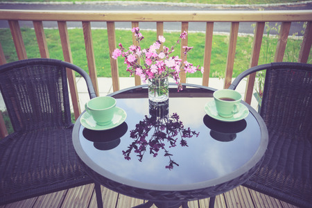 A table is set for tea outside on a porch photo