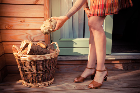 log deck: A young woman on a porch is getting logs from a basket to use as firewood
