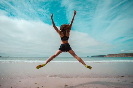 A young woman is doing star jumps on the beach by the sea