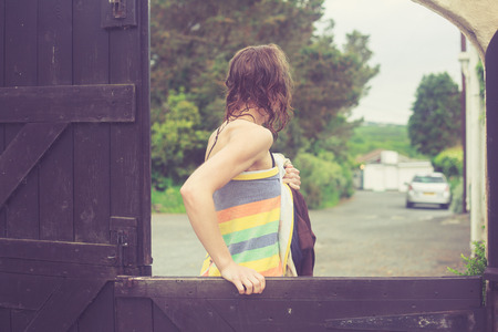 communal: A young woman wrapped in a towel is closing a gate outside on a farm