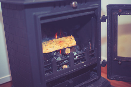 A traditional woodburner with a log burning photo