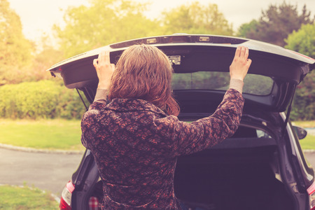 A young woman is opening the trunk of a car photo